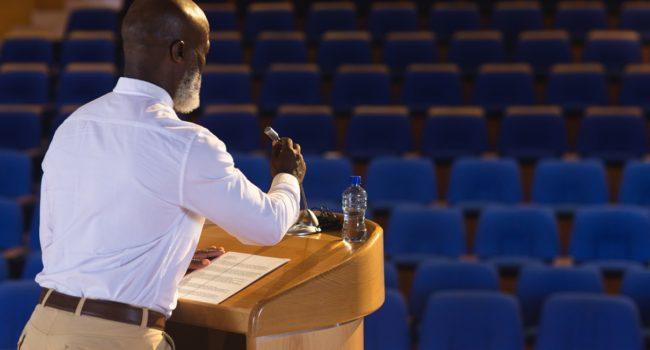 Matured businessman practicing for speech in the empty auditorium